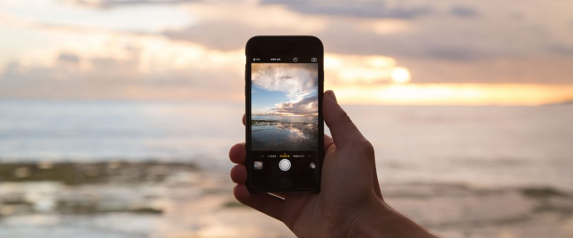 Hand holding a mobile phone while taking a picture of the sunrise over the ocean