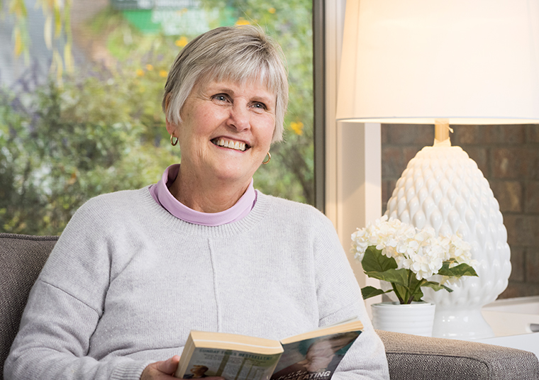 Older woman reading a book on the couch and smiling