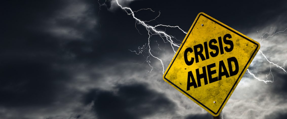 Crisis Ahead sign against a stormy background with lightning