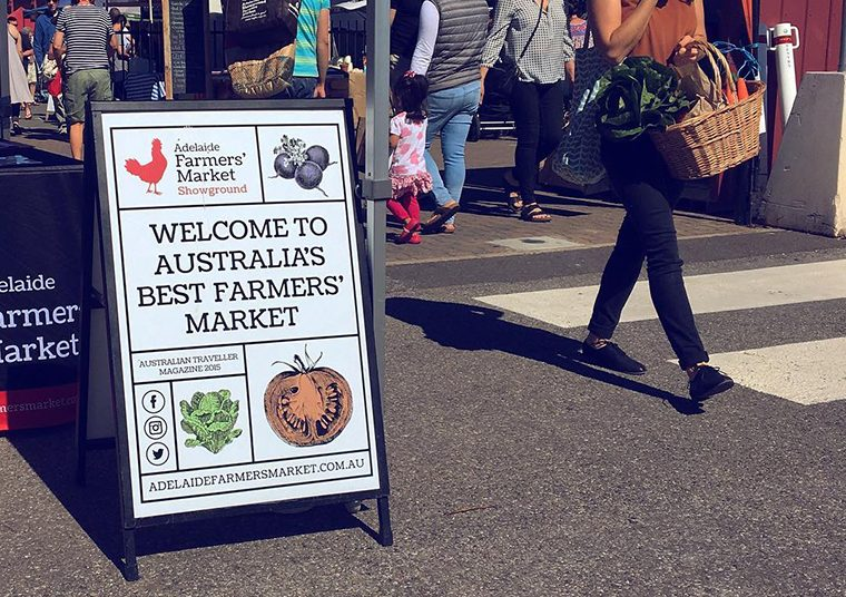 Adelaide Farmers' Market sandwich board signage designed by communikate with customers walking past carrying fresh, local produce