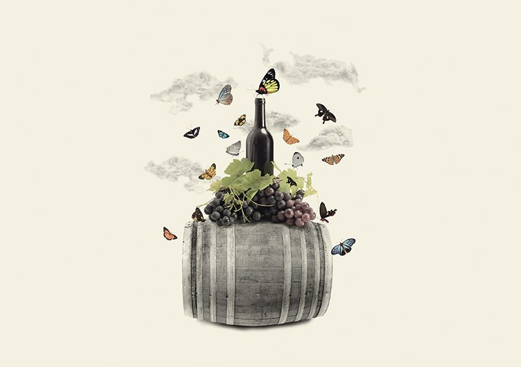 A bottle of wine and bunch of grapes sitting on top of a wine barrel, with many butterflies flying around