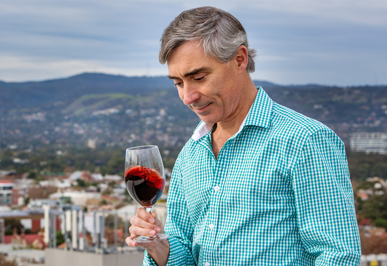 Man holding a wine glass swirling red wine around