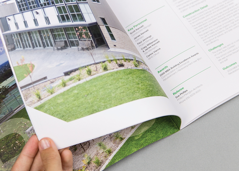 Hand turning a page in Kennett Builders booklet designed by communikate et al