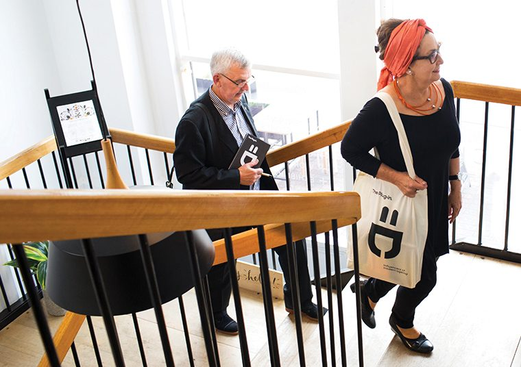 Older man and woman walking up the stairs on their way to a meeting holding The Plug-in collateral