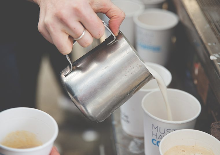 Barista pouring hot, frothy milk into a takeaway cup from a silver jug