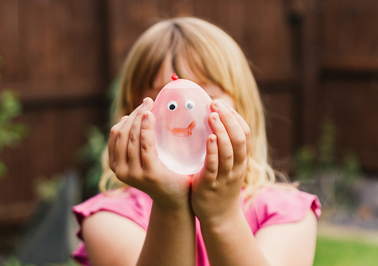Young girl holding a pink water balloon with a smiley face drawn on it in front of her face