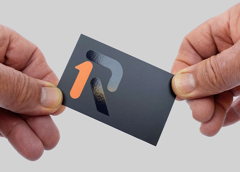 One Rail Australia business card designed by communikate held between two hands
