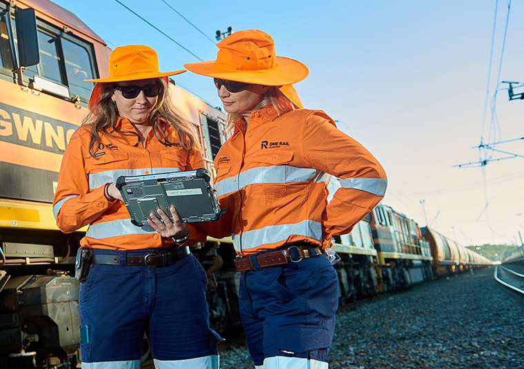 One Rail Australia staff checking something on an iPad as a One Rail train passes by
